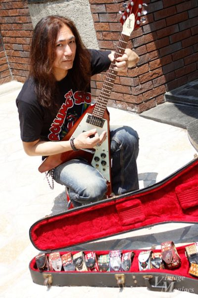 コレクションのヴィンテージストラップの横でギターを構えるHiroshi Takegami